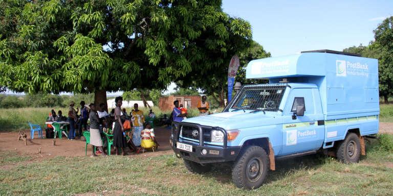 Un petit camion bleu de la Postbank stationne dans le camp de Rhino, en Ouganda, en novembre 2016.