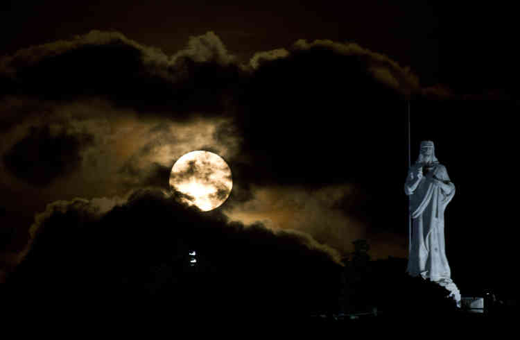 Partiellement cachée par les nuages derrière la statue du Christ de La Havane à Cuba.
