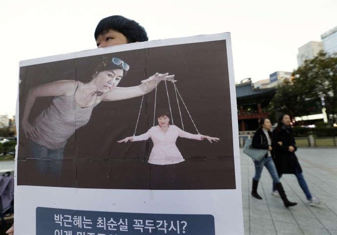 Pancarte montrant Choi Soon-sil en marionnettiste de la présidente sud-coréenne, Park Geun-hye, le 3novembre, à Séoul.