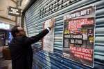 "A storekeeper puts a poster reading ""Opération ville morte"" on his closed store during a protest against the depopulation of the city center and the construction of a shopping mall in the outskirt of the town on November 18, 2016 in Montelimar, southeastern France. / AFP / PHILIPPE DESMAZES"