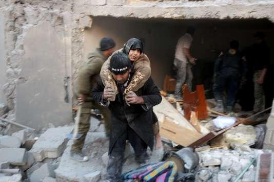 Un Syrien évacue une femme prise au piège d'un immeuble bombardé, à Alep, le 20 novembre.