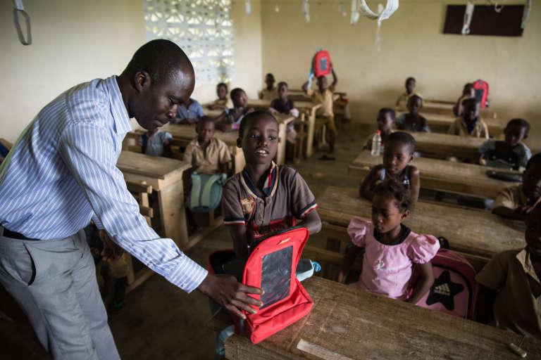 M. Nguettia, le directeur de l'école de Koroukro, vérifie les manuels présents dans le cartable solaire d'un élève.