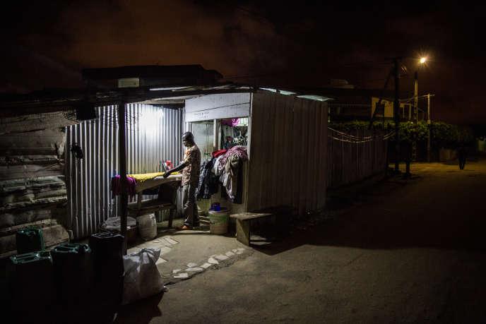 Abdallah travaille dans son échoppe, dans le quartier de la Palmeriaie, à Abidjan, jusque tard dans la nuit.