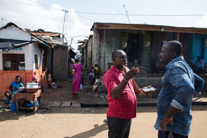 Raoul Loukou Kouassi avec un habitant du quartier du Campement, dans la banlieue d'Abidjan.