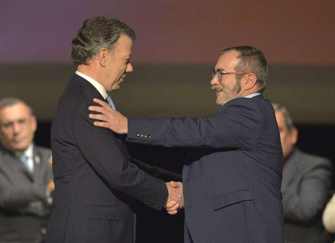 L'ancien président colombien Juan Manuel Santos (2010-2018, à gauche) et le chef des FARC, Rodrigo Londono, alias Timochenko, lors de la signature de l'accord de paix entre le gouvernement et les Forces armées colombiennes, le 24 novembre 2016, à Bogota.