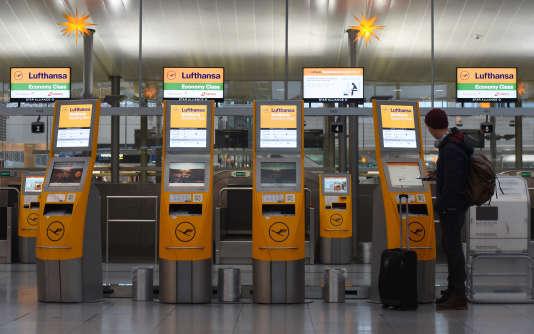Un passager patiente à un comptoir électronique à l'aéroport de Munich, le 24 novembre.