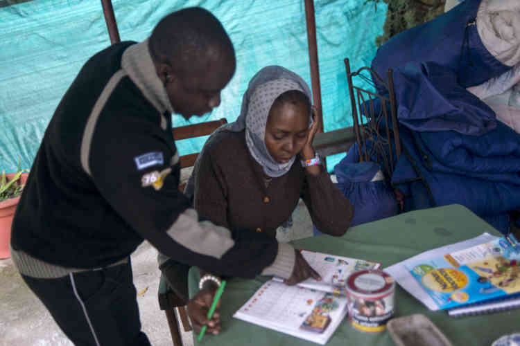 Mahamadou aide une famille soudanaise accueillie chez Françoise Cotta à apprendre le français.