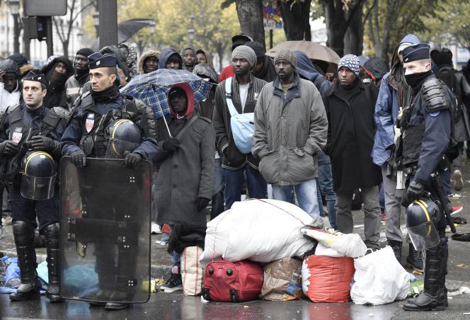 Des migrants attendent d'être évacués descampements près du métro Stalingrad, à Paris, vers des CAO en dehors de la capitale, le 4 novembre.