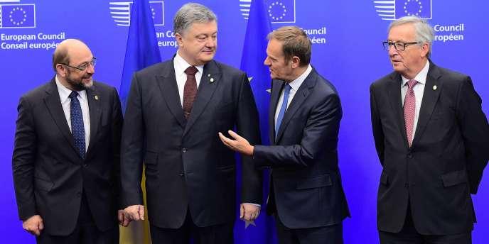 Le président ukrainien Petro Porochenko, entouré par le président du Parlement européen, Martin Schulz (à gauche), le président du Conseil européen, Donald Tusk(troisième à droite) et le président de la Commission européenne, Jean-Claude Juncker, en ouverture du sommet, à Bruxelles, le 24 novembre.