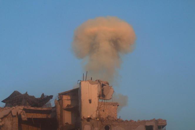Un nuage de fumée s'élève au dessus d'un immeuble d'un des quartiers tenus par les rebelles à Alep, le 26 novembre 2016.