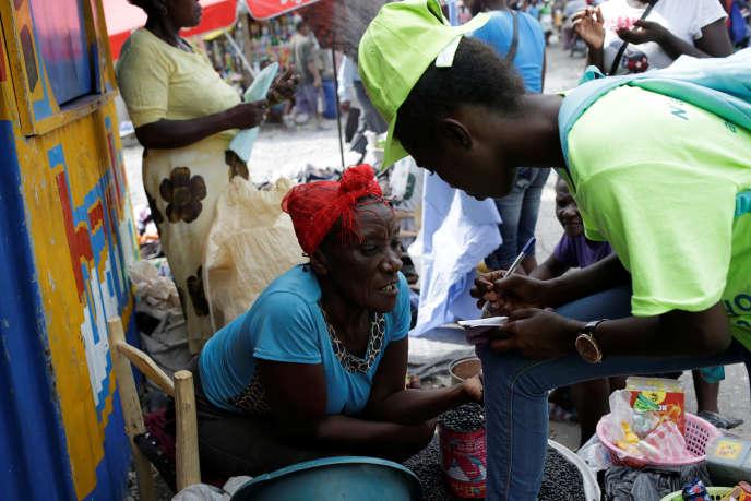 Une marchande de rue discute avec un membre de la campagne de vaccination anti-cholérique, à Cayes, en Haïti, le 8 novembre.