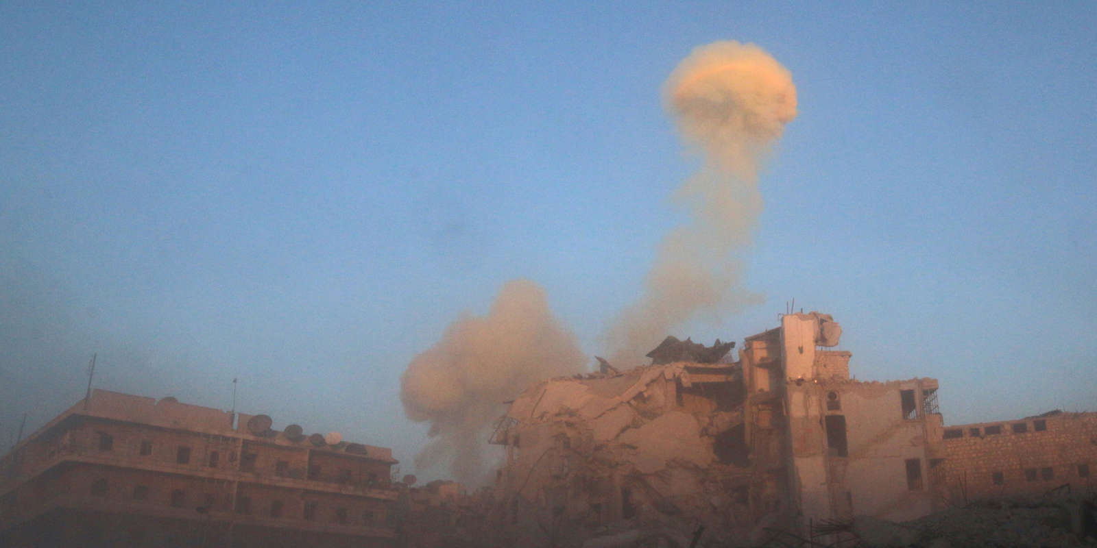 De la fumée s'élève après un bombardement dans le quartier d'Al-Chaar à Alep, en Syrie.