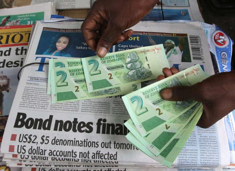 Un vendeur ambulant montre les nouveaux billets ou billets d'obligationà Harare, la capitale du Zimbabwe, le 28 novembre 2016.