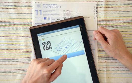 Une personne utilise une tablette près d'une déclaration papier des revenus de l'année 2012.