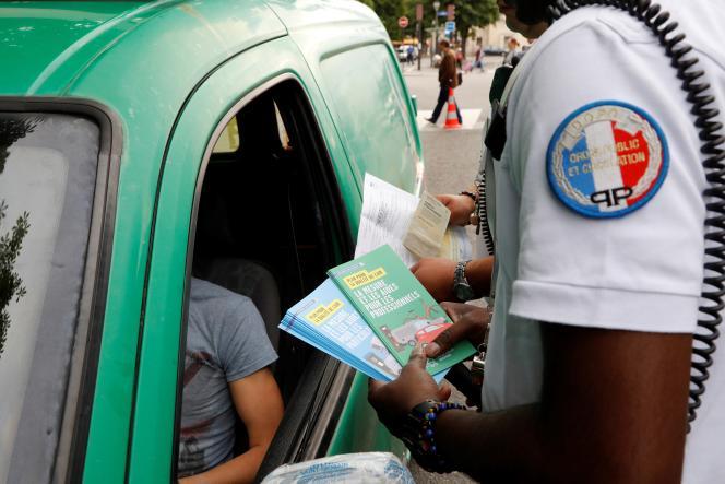 Un policier informe un automobiliste sur le plan antipollution, à Paris, le 1er juillet 2016.