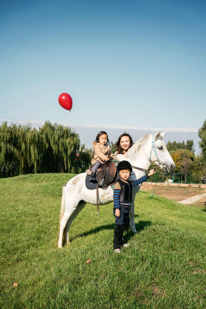 Le poney-club Ipony, près de Pékin, a ouvert en 2015. Ici, une mère pose avec ses enfants.