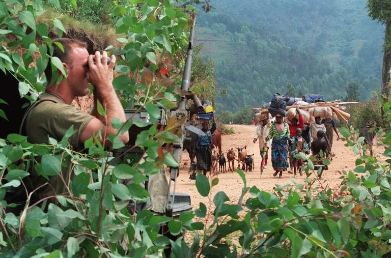 Des civils fuyant les combats sous la surveillance d'un soldat français près du camp de réfugiés de Kivum à l'ouest du Rwanda le 12 juillet 1994.