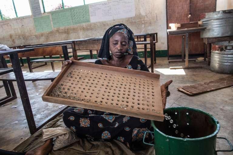 Préparation du scrutin dans un bureau de vote. En Gambie, on voteau moyen d'une bille à déposer dans des bidons de couleurs différentes, un par candidat.