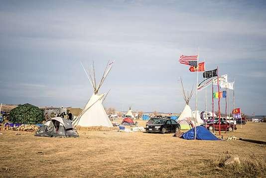 Le campement Oceti Sakowin,sur la réserve de Standing Rock. Des drapeaux indiens y côtoient le drapeau américain. Celui-ci est inversé, en signal de détresse extrême pour cause de menaces sur la vie ou la propriété.