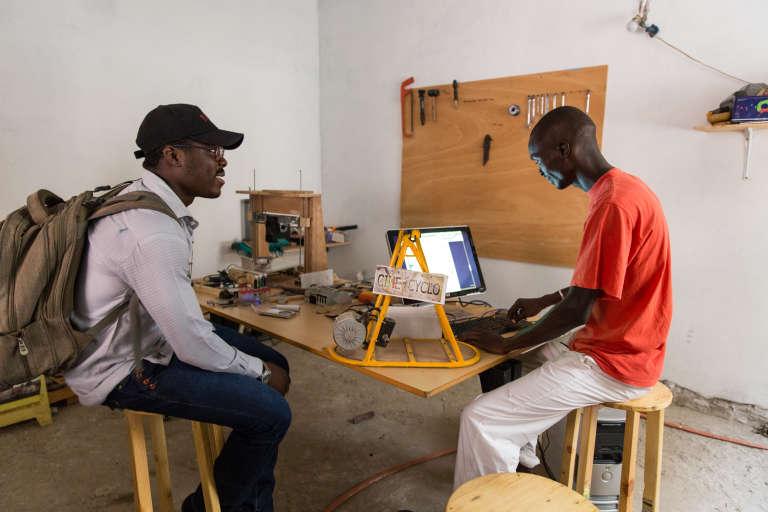 Cédric et Iba travaillantdans leur Cinécyclolab sur un prototype de génératrice.