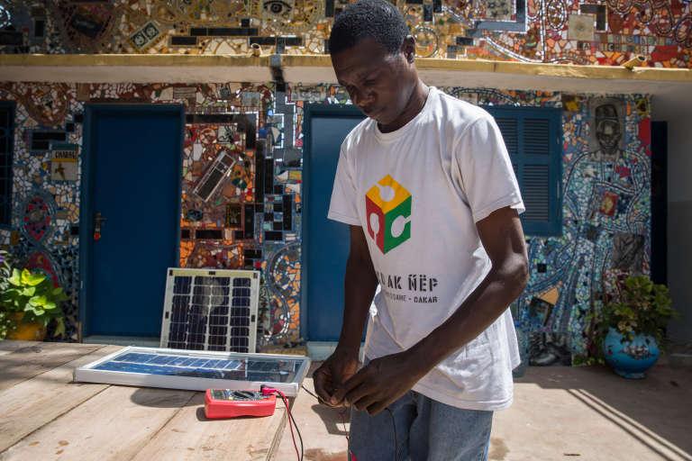 Modou travaille sur son prototype de panneau solaire.