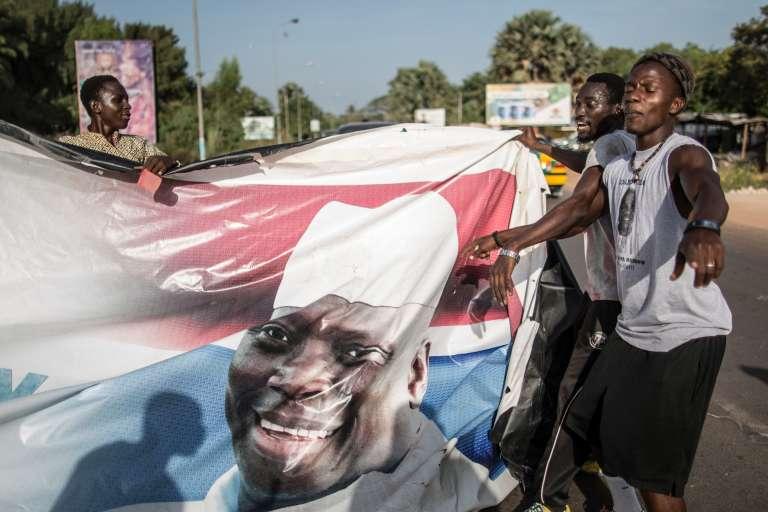 Des partisans du président élu déchirent des affiches de Yahya Jammeh, le 2 décembre, à Serekunda.
