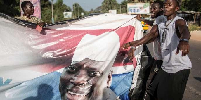 A Serrekunda, deuxième ville de Gambie, des partisans du nouveau président élu Adama Barrow arrachent un portrait de Yahya Jammeh, le 2 décembre 2016.