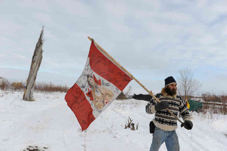Un homme porte le drapeau de la Nation indienne pour protester contre le projet d'oléoduc aux abords de la réserve de Standing Rock, le 2 décembre.