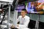 Un trader sur devises à Tokyo au travail alors que Matteo Renzi s'exprime à la télévision, le 5 décembre.