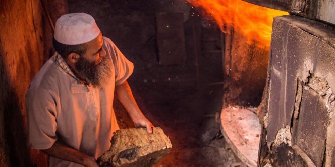 Un «farnatchi» alimente une chaudière traditionnelle dans un hammam.