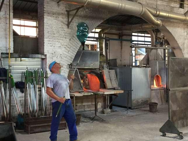 Le maître verrier allonge sa création par de grands moulinets avec sa canne, chez Venini, à Murano.