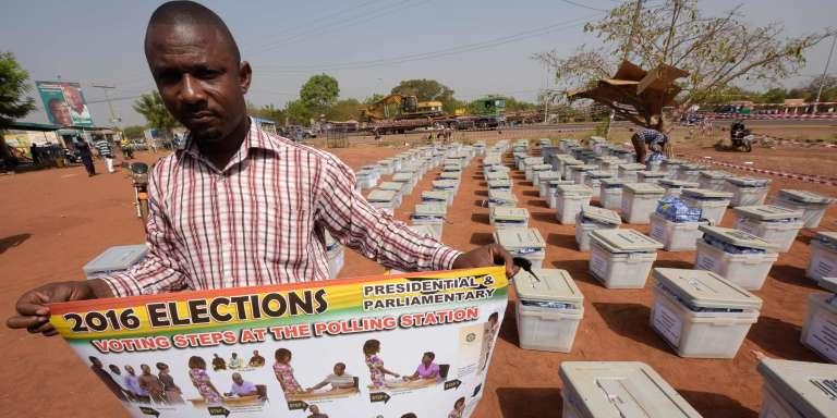 Un responsable de la Commission électorale tient une affiche devant être utilisée dans chaque bureau de vote, à la veille des élections présidentielle et législatives, à Tamale (nord du Ghana), le 6 décembre.