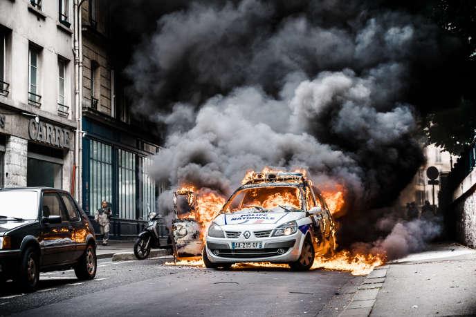«les policiers sont aussi des citoyens. Or c'est toute notre société qui va mal et le moral d'un peu tout le monde qui est « plombé ». Et ce, pas seulement à cause des attentats» (Photo: un groupe incendie une voiture de police le long du Canal Saint-Martin, après avoir fait sortir de force les deux policiers qui se trouvaient dans le véhicule, à Paris, le 18 mai 2016).