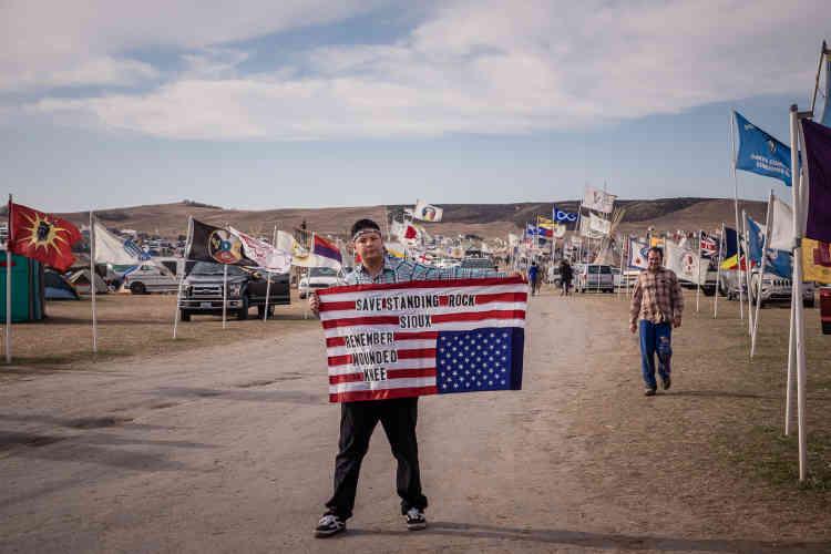 D'avril à décembre 2016, les Indiens dela réserve sioux de Standing Rock,dans le Dakota du Nord, se sont mobilisés contre le projet de passage sur leurs terres d'un oléoduc transportant du gaz de schiste. En novembre, le photographe Matt Hamon a passé quelques jours avec les manifestants,dans le camp d'Oceti Sakowin. Sur le drapeau américain déployé parun manifestant, un message fait référence au massacre de Wounded Knee, dans le Dakota du sud,où, en1890, plusieurs centaines d'Indiens furent tués par la cavalerie.
