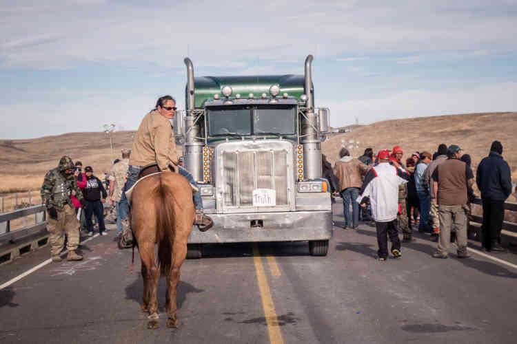 Le 6 novembre 2016, sur le Backwater Bridge, non loin du camp de Standing Rock, une femme à cheval encadreune marche de la paix.