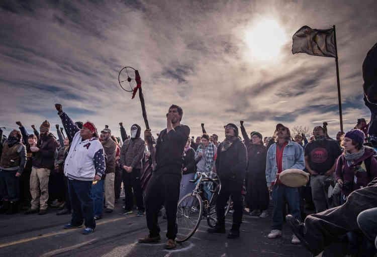 6 novembre 2016. Les manifestants défient les forces armées qui occupent le Backwater Bridge au cri de « mni wiconi!» (« l'eau, c'est la vie » en langue Lakota). L'undes leaders de la lutte anti-pipeline (enblanc, à gauche)estun descendant deSitting Bull.
