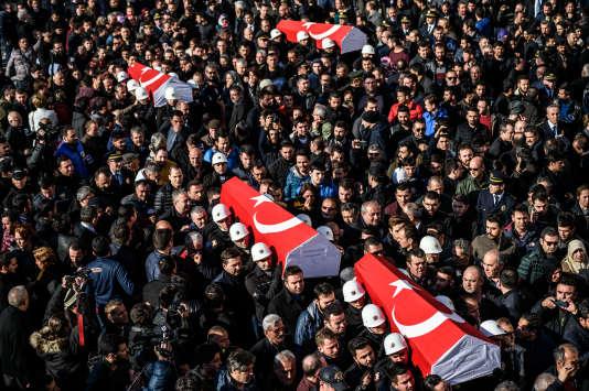 Des policiers portent des cercueils, le 11 décembre à Istanbul en Turquie.