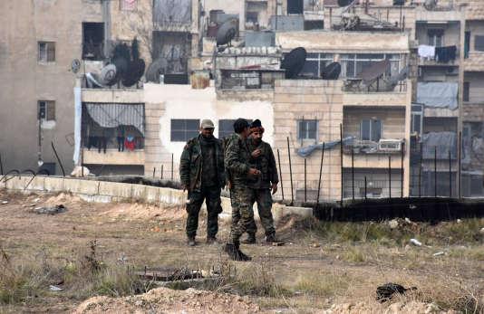 Des membres des forces gouvernementales marchent, le11décembre, dans le quartier d'Ithaa, situé dans l'ouest d'Alep, après avoir repris les quartiers est aux rebelles.