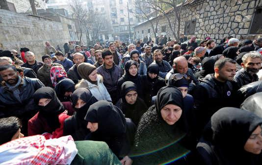 Des civils attendent devant un bâtiment gouvernemental pour rendre visite à leurs familles évacuées d'Alep-Est, le 11 décembre 2016.
