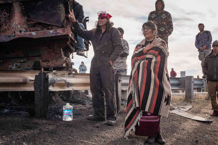 Jaylyn Gough, de la tribu Navajo, ici accompagnéed'autres soutiens des Sioux, fait face aux forces de l'ordre, malgré les menaces d'aspersionde gaz lacrymogène.