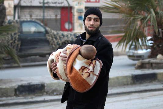 Un homme fuit avec un enfant dans les ruines d'Alep, le 12 décembre 2016.