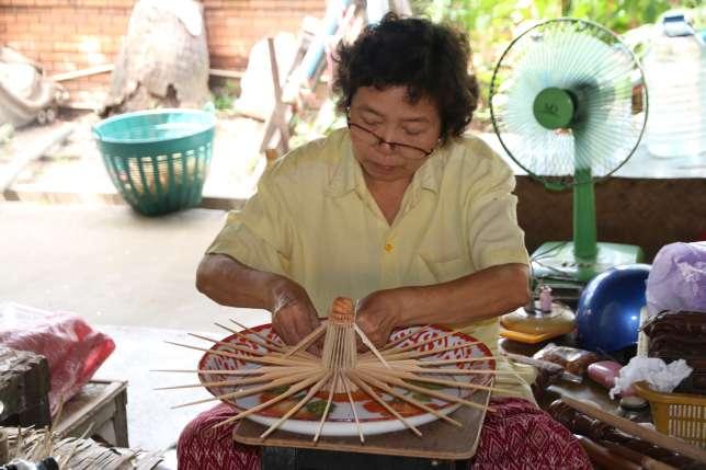 Dans les faubourgs de la ville, une femme fabrique des ombrelles avec des matériaux naturels.