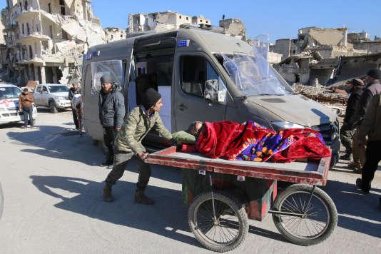 Un homme pousse une femme allongée vers un véhicule chargé d'évacuer les civils d'Alep, jeudi 15 décembre.