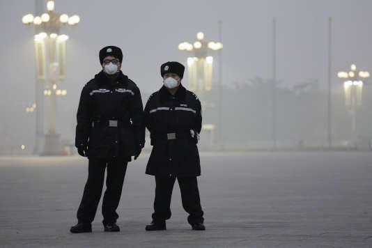 Deux policiers portent un masque antipollution sur la place Tiananmen, le1erdécembre 2015.