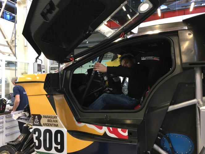 Sébastien Loeb se glisse dans sa 3008 DKR pour régler siège et écrans, le 14décembre chez PSA Vélizy-Villacoublay (Yvelines).