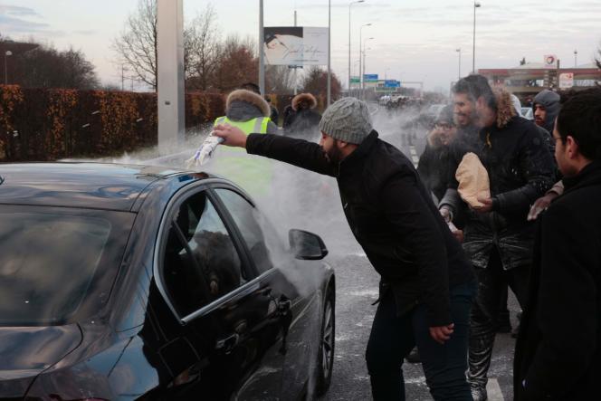 Un chauffeur de VTC jette du lait sur une voiture lors d'un blocus de l'autoroute menant à l'aéroport Charles-de-Gaulle, le 16décembre, à Roissy-en-France.