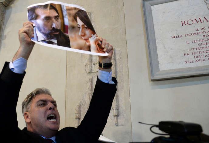 Un conseiller municipal de l'opposition brandit une feuille avec les photos de la maire de Rome, Virginia Raggi, et son chef des ressources humaines, Raffaele Marra, lors d'une manifestation au Capitole, le 16 décembre 2016.