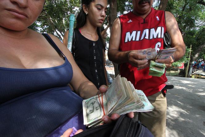 Des Vénézueliens tentent d'échanger leurs devises, dont le retrait a été décidé.