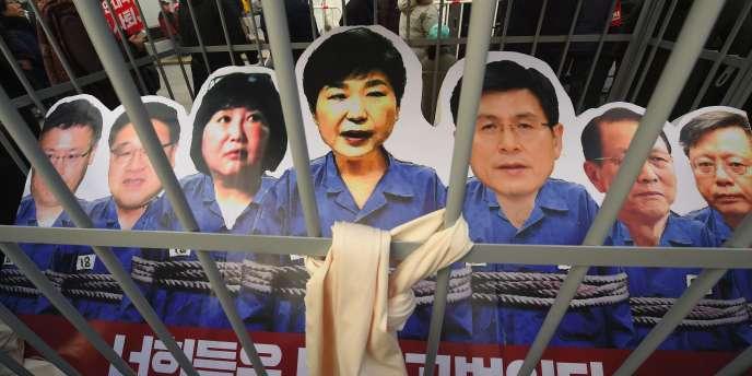 Des portrait de la présidente Park et de son entourage, représentés derrière les barreaux pour protester contre le régime actuel.