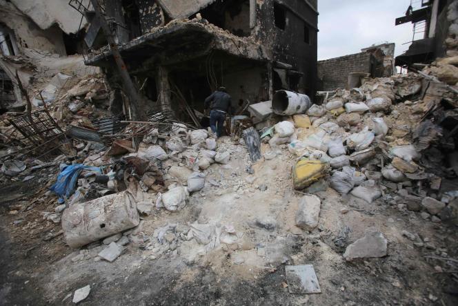 Un homme inspecte les décombres d'un immeuble dans la vieille ville d'Alep, en Syrie.